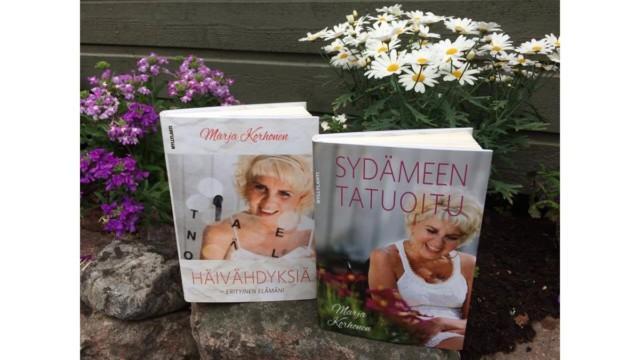 Kiven päällä aseteltuna kaksi Marja Korhosen kirjaa, taustalla kukkakimppuja