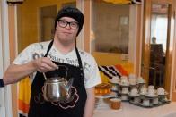 Henkilö pitää kädessään kuparista kahvipannua ja taustalla näkyy kahvilan herkkuja pöydällä.