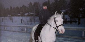 Valkoisen hevosen selässä ratsastaa tummiin pukeutunut nuori nainen. Taustalla on luminen pihamaa.