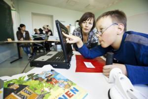 Poika tutkii etusormella kosketusnäyttöä koulussa. Taustalla opettaja tarkkailee hänen työskentelyään ja katsoo myös näyttöä.