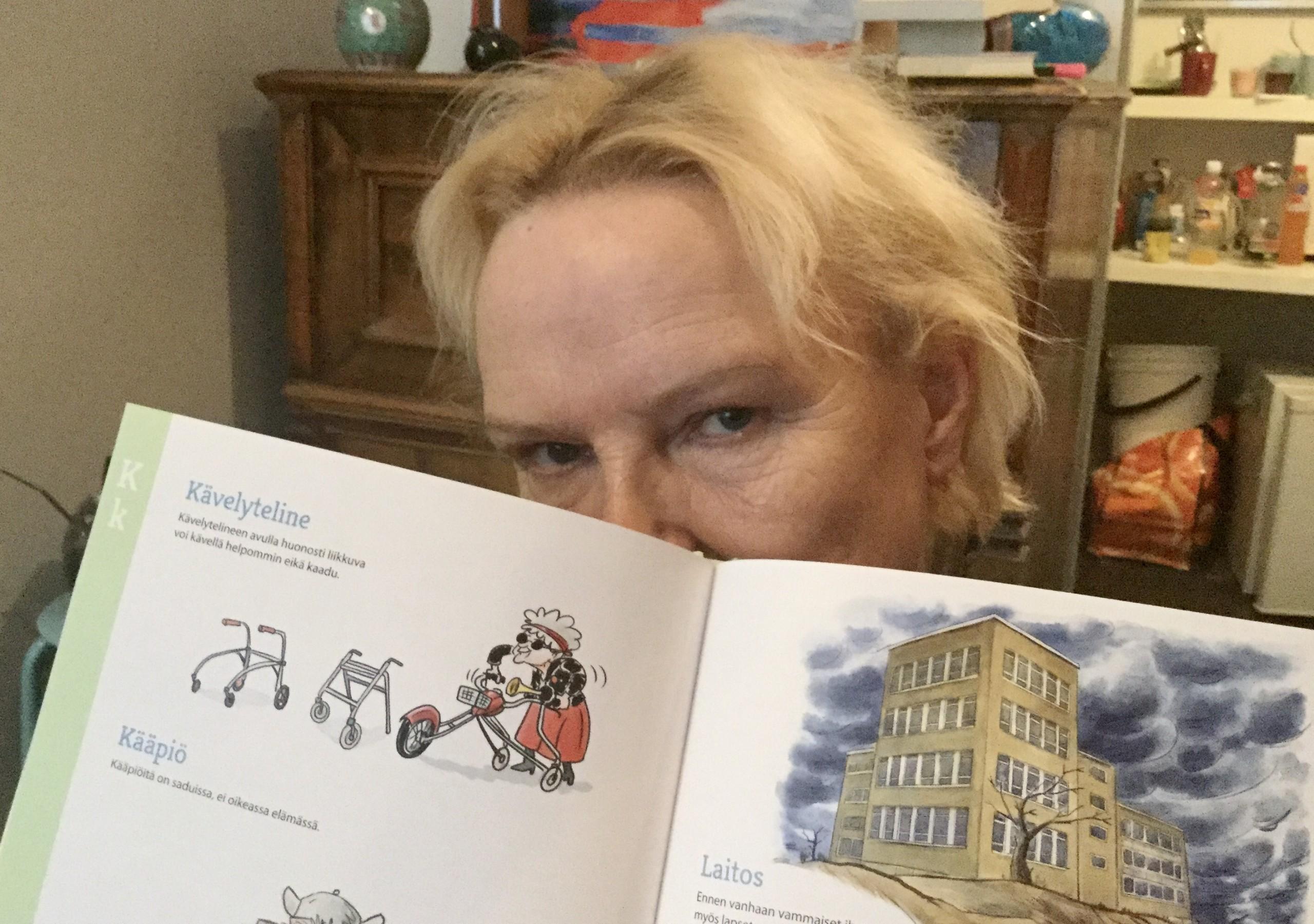Nainen, jolla on vakava ilme, piilottaa kasvonsa puolittain avatun kirjan taakse. Kirjassa kerrotaan humoristisesti vammaistermeistä.
