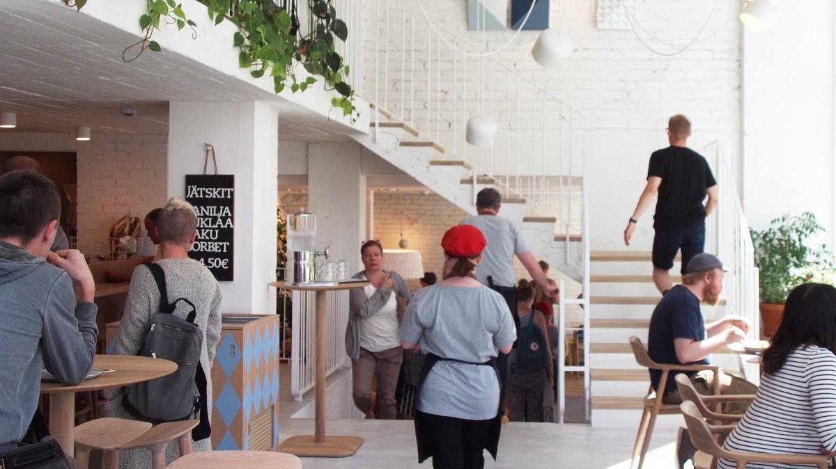 Kuva kahvilan sisäpuolelta. Kuvassa portaat kahvilan yläkertaan sekä asikkaita ja työntekijöitä.