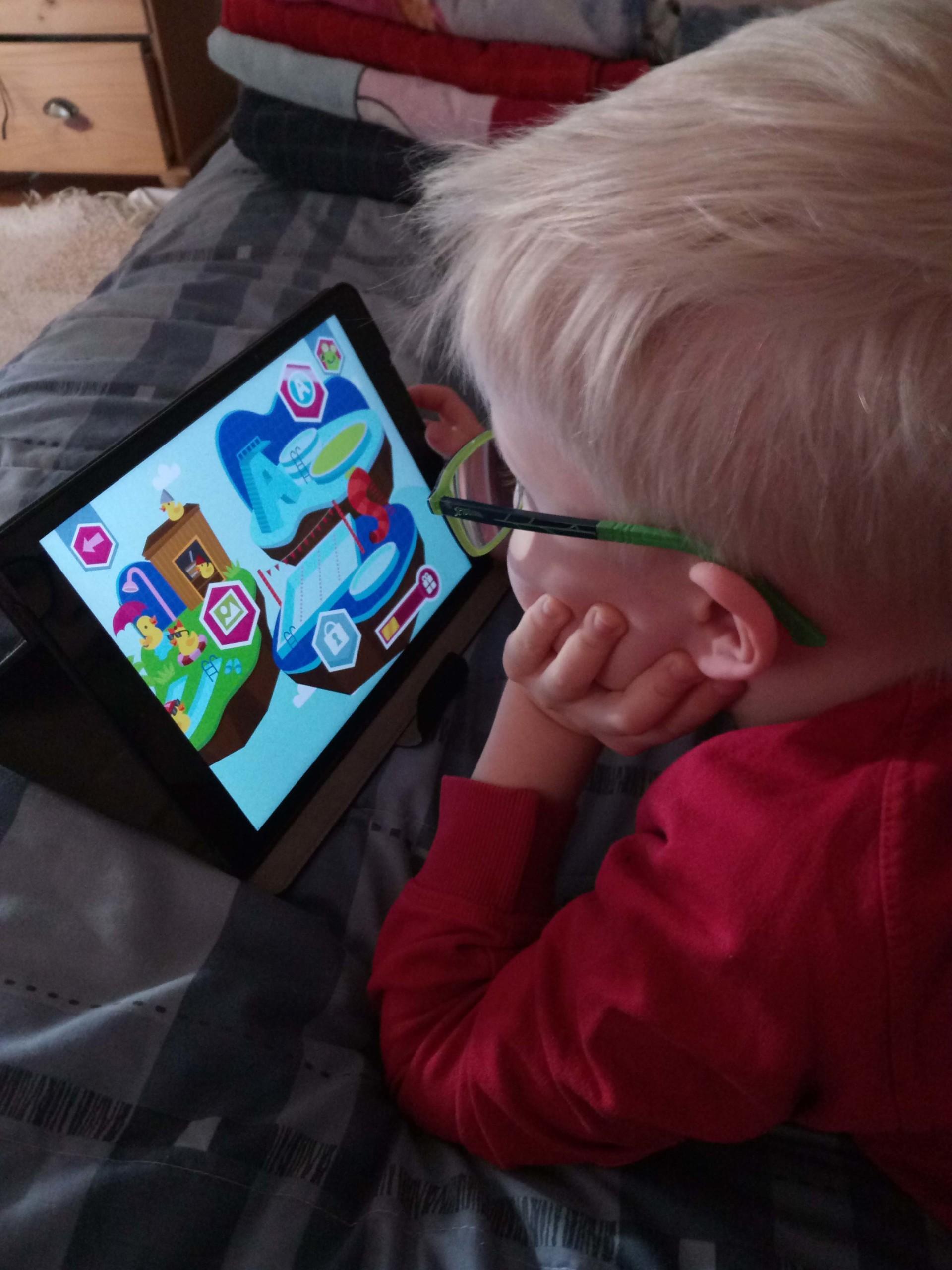 Kuvassa punapaitainen poika pelaa taböetilla värikästä oppimispeliä. Pojalla on vaaleat hiukset ja vihreät silmälasit. Poika on selin kameraan.