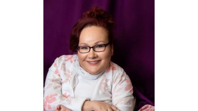 Kuvassa hymyilevä naishenkilö, jolla on punainen tukka, vaalean sävyinen paita sekä tummat silmälasit