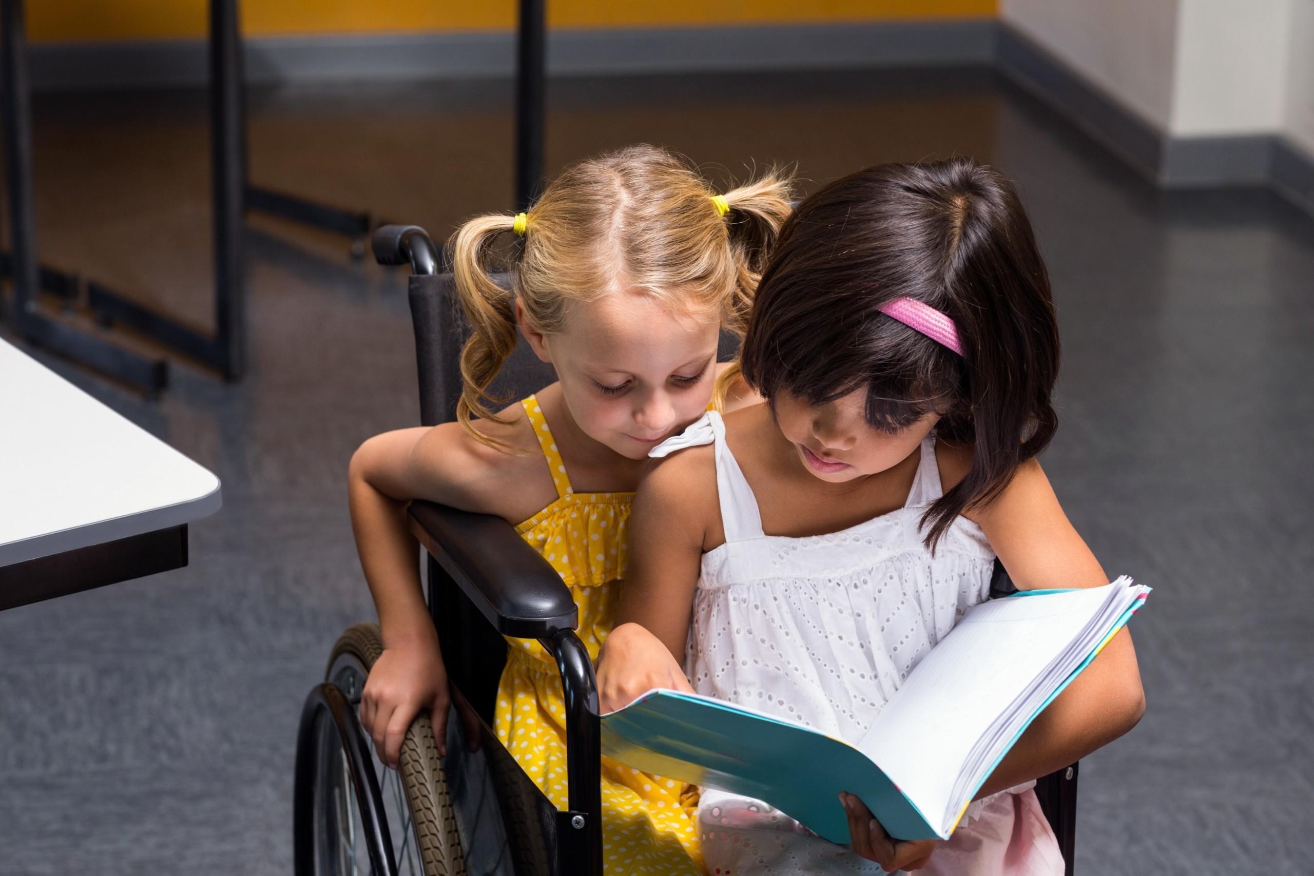 Kaksi lasta istuu sylikkäin pyörätuolissa ja lukevat kirjaa
