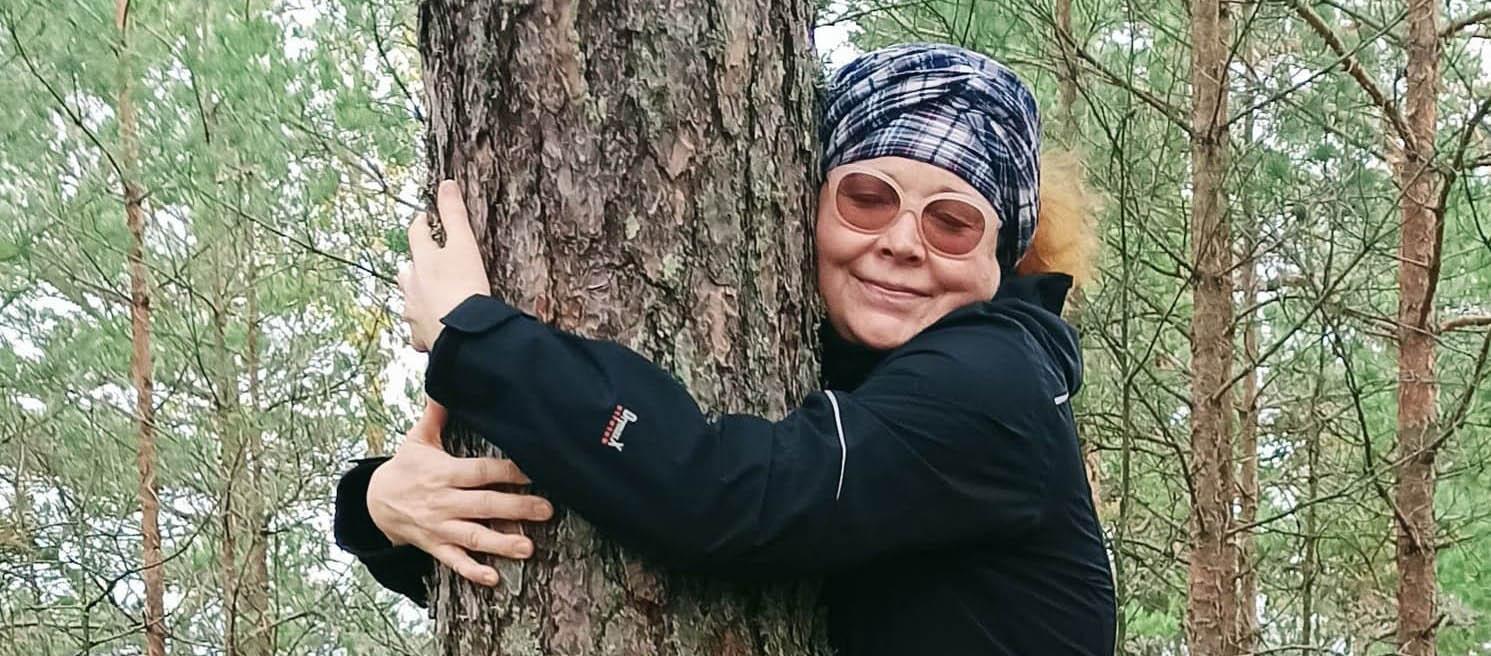 Huivipäinen, tummapuseroinen hymyilevä nainen aurinkolasit päässä, halaa puuta.