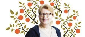 Silmälasipäinen vaalea nainen hymyilee vasempaan yläviistoon, taustalla piirretty omenapuu punaisine omenoineen.