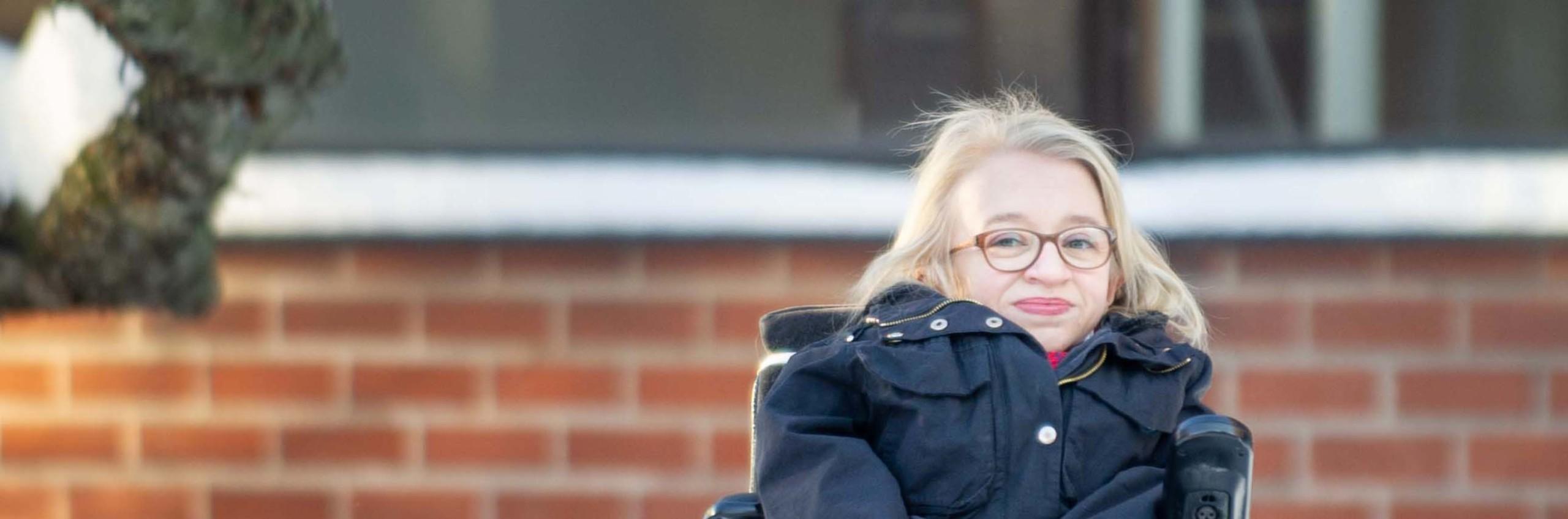 Vaalea- ja pitkätukkainen, silmälasipäinen nainen istuu tummassa takissa pyörätuolissa. koulun pihalla.